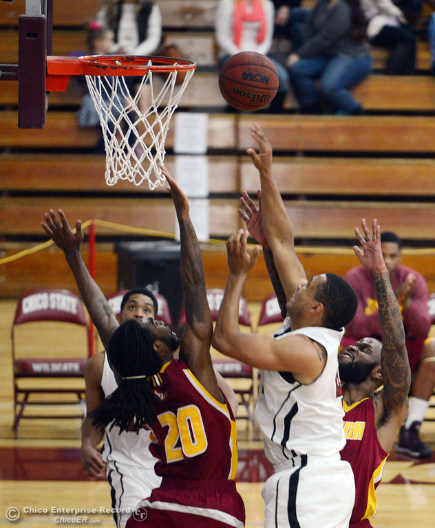 . Chico State\'s #41 Jordan Barton (right) takes a shot against Cal State Dominguez Hills\' #20 Steffon Neal (left) in the first half of their men\'s basketball game at CSUC Acker Gym Friday, January 10, 2014 in Chico, Calif.  (Jason Halley/Chico Enterprise-Record)