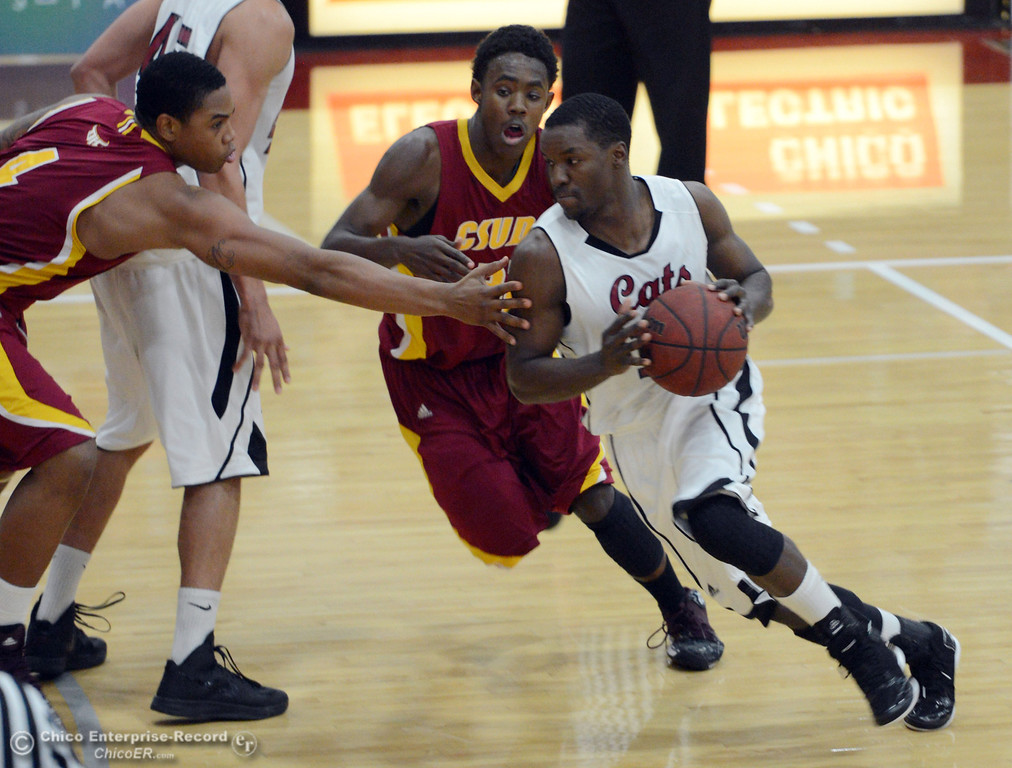 . Chico State\'s #11 Rashad Parker (right) dribbles against Cal State Dominguez Hills\' #32 Everett Turner (center) and #4 Darnell Martin (left) in the first half of their men\'s basketball game at CSUC Acker Gym Friday, January 10, 2014 in Chico, Calif.  (Jason Halley/Chico Enterprise-Record)