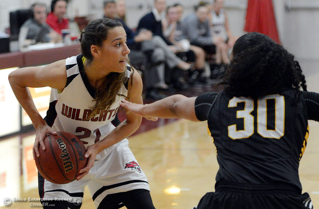 . Chico State\'s #21 Courtney Hamilton (left) looks to pass against Cal State L.A.\'s #30 Kaija Powell (right) in the first half of their women\'s basketball game at CSUC Acker Gym Saturday, January 11, 2014 in Chico, Calif.  (Jason Halley/Chico Enterprise-Record)