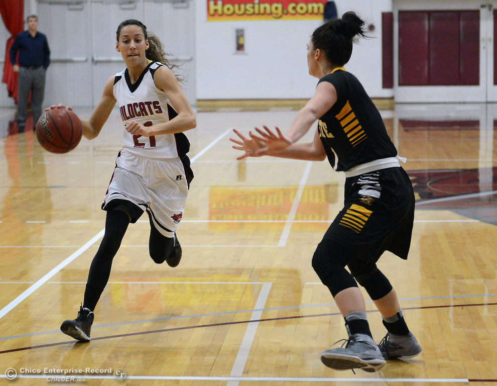. Chico State\'s #21 Courtney Hamilton (left) dribbles against Cal State L.A.\'s #1 Paige Melville (right) in the first half of their women\'s basketball game at CSUC Acker Gym Saturday, January 11, 2014 in Chico, Calif.  (Jason Halley/Chico Enterprise-Record)