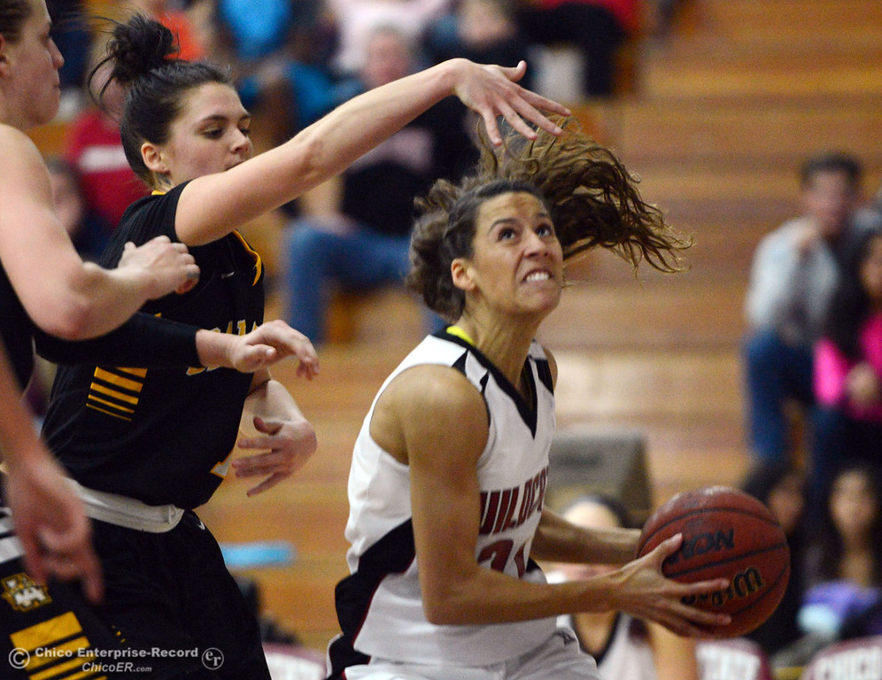 . Chico State\'s #21 Courtney Hamilton (right) goes up for a shot against Cal State L.A.\'s #1 Paige Melville (left) in the second half of their women\'s basketball game at CSUC Acker Gym Saturday, January 11, 2014 in Chico, Calif.  (Jason Halley/Chico Enterprise-Record)