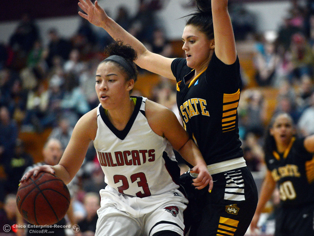 . Chico State\'s #23 Jazmine Miller (left) dribbles against Cal State L.A.\'s #1 Paige Melville (right) in the second half of their women\'s basketball game at CSUC Acker Gym Saturday, January 11, 2014 in Chico, Calif.  (Jason Halley/Chico Enterprise-Record)