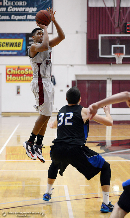 . Chico State\'s #15 Amir Carraway (left) takes a shot against Cal State San Bernardino\'s #32 Taylor Statham (right) in the first half of their men\'s basketball game at CSUC Acker Gym Saturday, February 8, 2014 in Chico, Calif.  (Jason Halley/Chico Enterprise-Record)