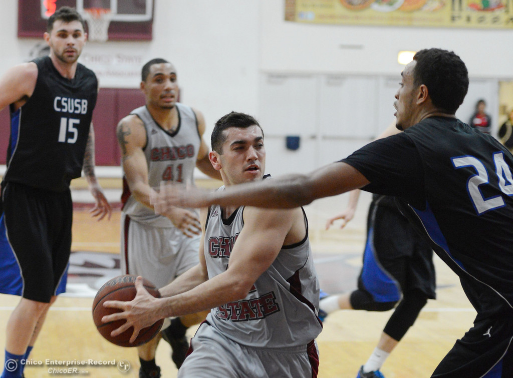 . Chico State\'s #12 Giordano Estrada (left) dribbles against Cal State San Bernardino\'s #24 Jordan Burris (right) in the second half of their men\'s basketball game at CSUC Acker Gym Saturday, February 8, 2014 in Chico, Calif.  (Jason Halley/Chico Enterprise-Record)