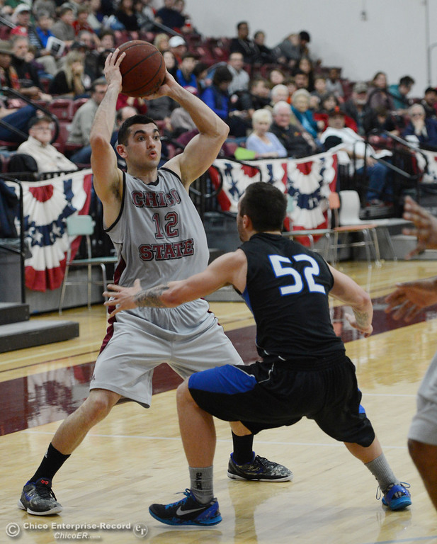 . Chico State\'s #12 Giordano Estrada (left) looks to pass against Cal State San Bernardino\'s #52 Zeke DeBlase (right) in the second half of their men\'s basketball game at CSUC Acker Gym Saturday, February 8, 2014 in Chico, Calif.  (Jason Halley/Chico Enterprise-Record)