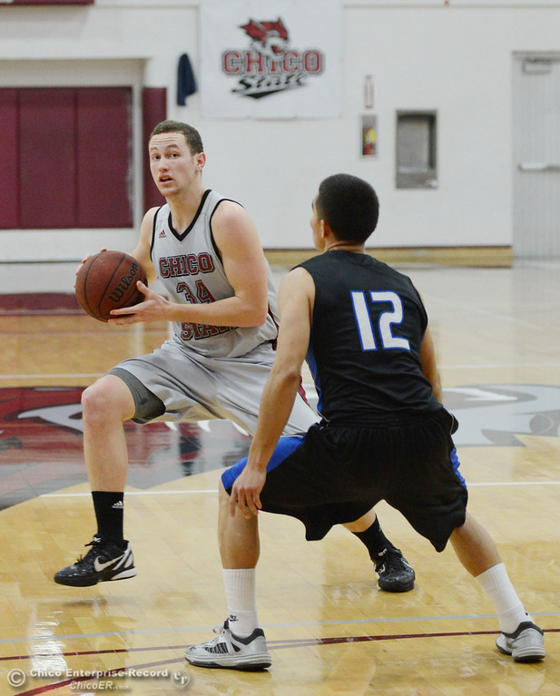 . Chico State\'s #32 Drew Kitchens (left) dribbles against Cal State San Bernardino\'s #12 Juan Martinez (right) in the first half of their men\'s basketball game at CSUC Acker Gym Saturday, February 8, 2014 in Chico, Calif.  (Jason Halley/Chico Enterprise-Record)