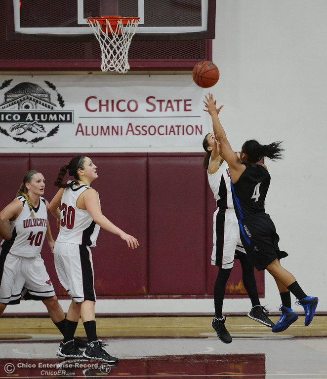 . Chico State\'s #21 Courtney Hamilton (left) attempts to block against Cal State San Bernardino\'s #4 Alexcia Mack (right) in the second half of their women\'s basketball game at CSUC Acker Gym Saturday, February 8, 2014 in Chico, Calif.  (Jason Halley/Chico Enterprise-Record)
