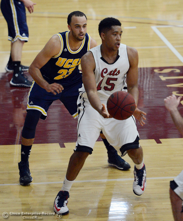 . Chico State\'s #15 Amir Carraway (right) passes against UC San Diego\'s #23 Hunter Walker (left) in the first half of their men\'s basketball game at CSUC Acker Gym Friday, February 7, 2014 in Chico, Calif.  (Jason Halley/Chico Enterprise-Record)