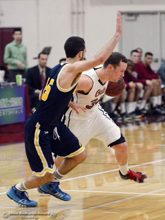 . Chico State\'s #34 Drew Kitchens (right) dribbles against UC San Diego\'s #15 Aleks Lipovic (left) in the first half of their men\'s basketball game at CSUC Acker Gym Friday, February 7, 2014 in Chico, Calif.  (Jason Halley/Chico Enterprise-Record)