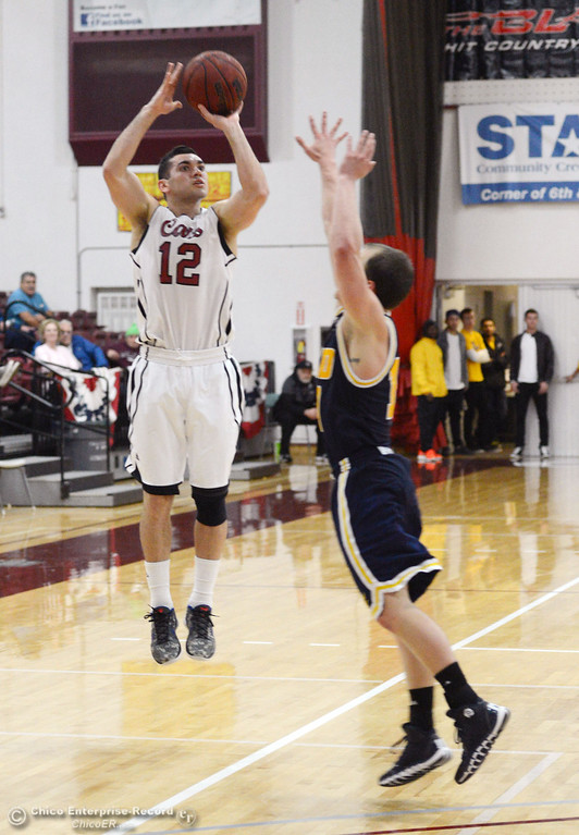 . Chico State\'s #12 Giordano Estrada (left) takes a shot against UC San Diego\'s #10 James McCann (right) in the second half of their men\'s basketball game at CSUC Acker Gym Friday, February 7, 2014 in Chico, Calif.  (Jason Halley/Chico Enterprise-Record)