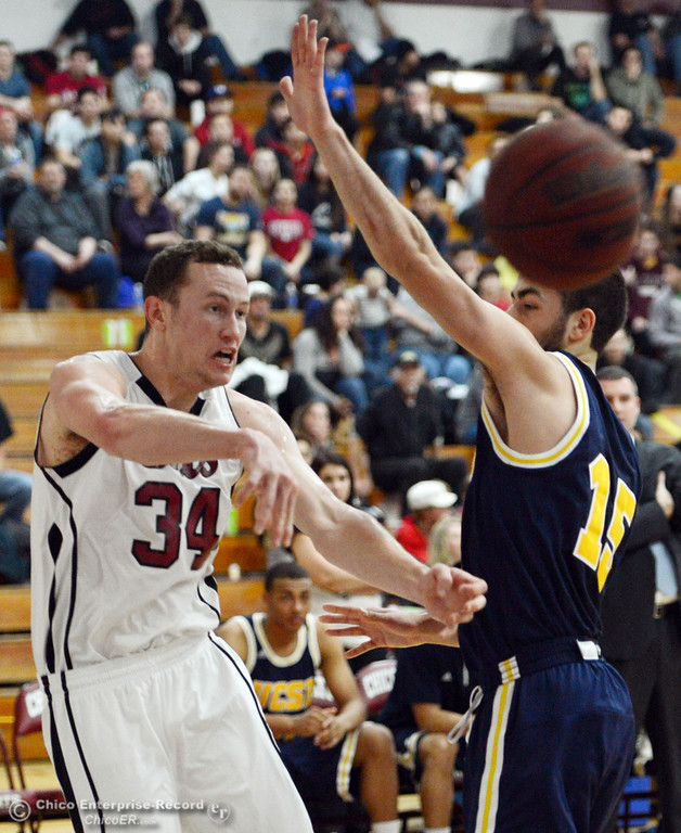 . Chico State\'s #34 Drew Kitchens (left) passes against UC San Diego\'s #15 Aleks Lipovic (right) in the first half of their men\'s basketball game at CSUC Acker Gym Friday, February 7, 2014 in Chico, Calif.  (Jason Halley/Chico Enterprise-Record)
