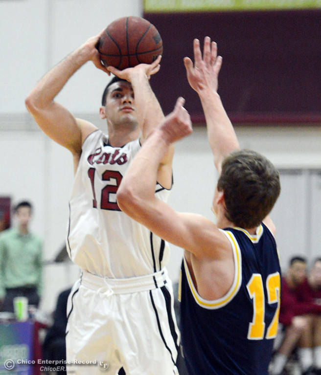 . Chico State\'s #12 Giordano Estrada (left) takes a shot against UC San Diego\'s #12 Adam Klie (right) in the first half of their men\'s basketball game at CSUC Acker Gym Friday, February 7, 2014 in Chico, Calif.  (Jason Halley/Chico Enterprise-Record)