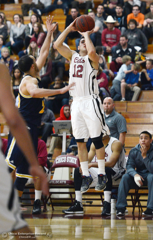. Chico State\'s #12 Giordano Estrada (right) takes a shot against UC San Diego\'s #24 Treavon Francis (left) in the second half of their men\'s basketball game at CSUC Acker Gym Friday, February 7, 2014 in Chico, Calif.  (Jason Halley/Chico Enterprise-Record)