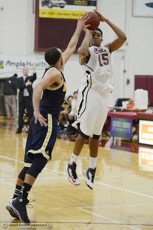 . Chico State\'s #15 Amir Carraway (right) takes a shot against UC San Diego\'s #23 Hunter Walker (left) in the second half of their men\'s basketball game at CSUC Acker Gym Friday, February 7, 2014 in Chico, Calif.  (Jason Halley/Chico Enterprise-Record)