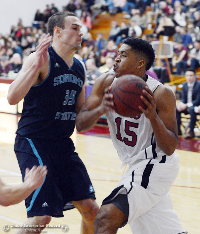 . Chico State\'s #15 Amir Carraway (right) dribbles against Sonoma State\'s #35 Justin Herold (left) in the second half of their men\'s basketball game at CSUC Acker Gym Friday January 31, 2014 in Chico, Calif. (Jason Halley/Chico Enterprise-Record)