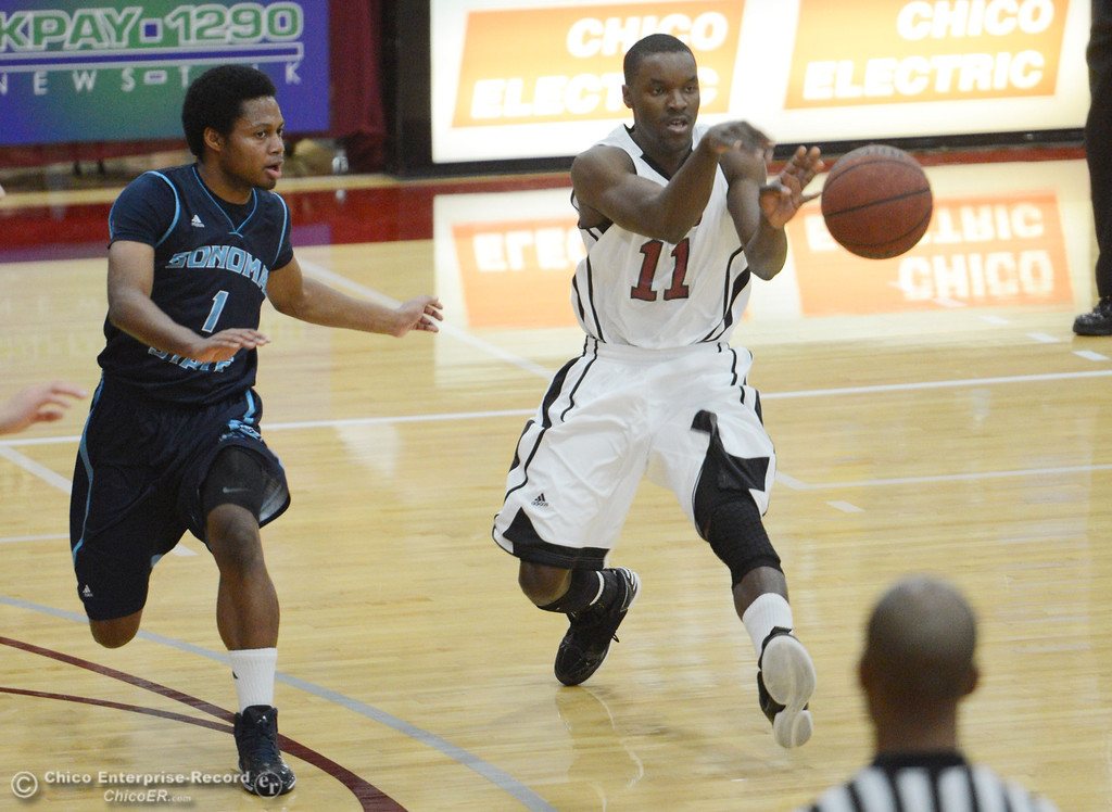 . Chico State\'s #11 Rashad Parker (right) passes against Sonoma State\'s #1 Khalid Johnson (left) in the first half of their men\'s basketball game at CSUC Acker Gym Friday January 31, 2014 in Chico, Calif. (Jason Halley/Chico Enterprise-Record)