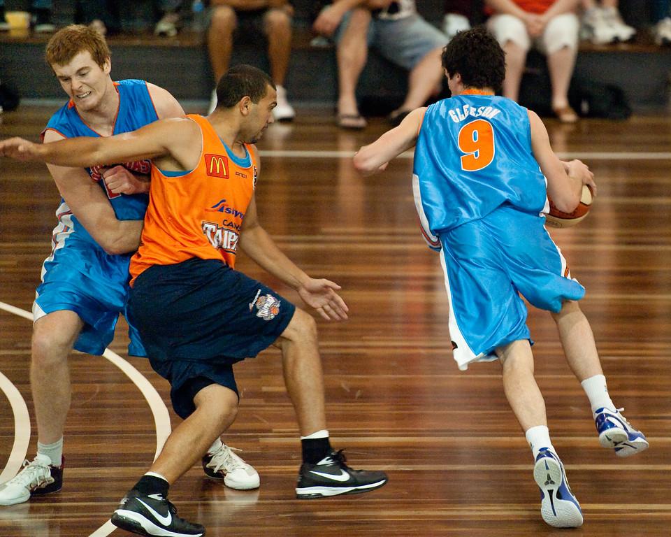 """Tom Garlepp sets a screen on Kerry Williams to get Jason Cadee free - Cairns Taipans v Gold Coast Blaze Pre-season  NBL Basketball, Auchenflower, Brisbane, Queensland, Australia; 3 September 2011. Photos by Des Thureson:  <a href=""""http://disci.smugmug.com"""">http://disci.smugmug.com</a>."""