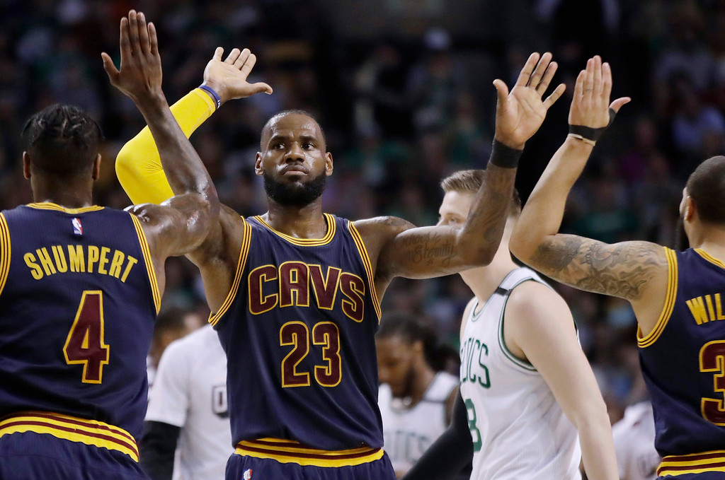 . Cleveland Cavaliers forward LeBron James trades high-fives with teammates Iman Shumpert, left, and Deron Williams, right, during the first half of Game 2 of the NBA basketball Eastern Conference finals against the Boston Celtics, Friday, May 19, 2017, in Boston. (AP Photo/Elise Amendola)