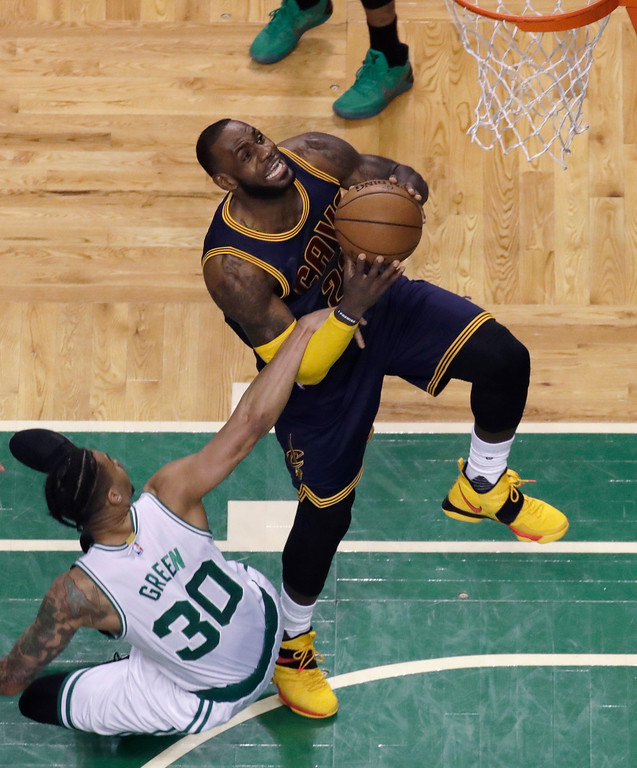 . Cleveland Cavaliers forward LeBron James (23) drives against Boston Celtics forward Gerald Green (30) hanging on during first half of Game 2 of the NBA basketball Eastern Conference finals, Friday, May 19, 2017, in Boston. (AP Photo/Elise Amendola)