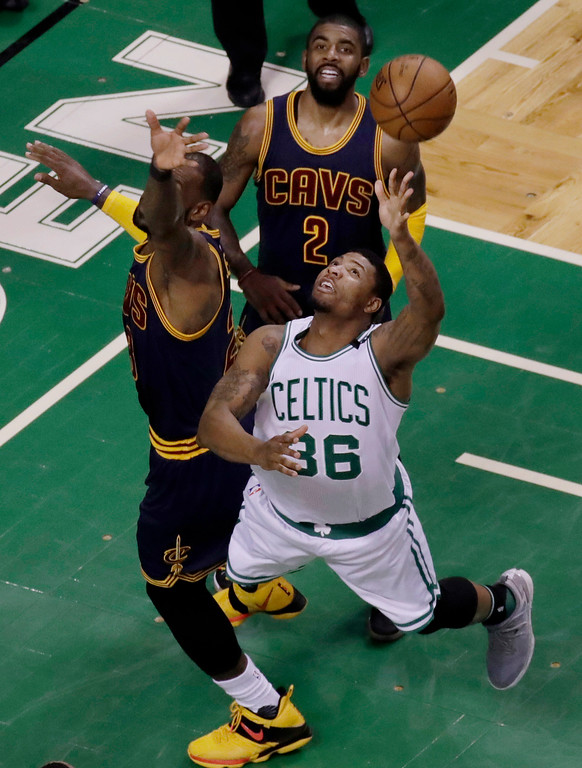 . Boston Celtics guard Marcus Smart (36) fights for the ball between Cleveland Cavaliers forward LeBron James, left, and guard Kyrie Irving, rear, during first half of Game 2 of the NBA basketball Eastern Conference finals, Friday, May 19, 2017, in Boston. (AP Photo/Elise Amendola)