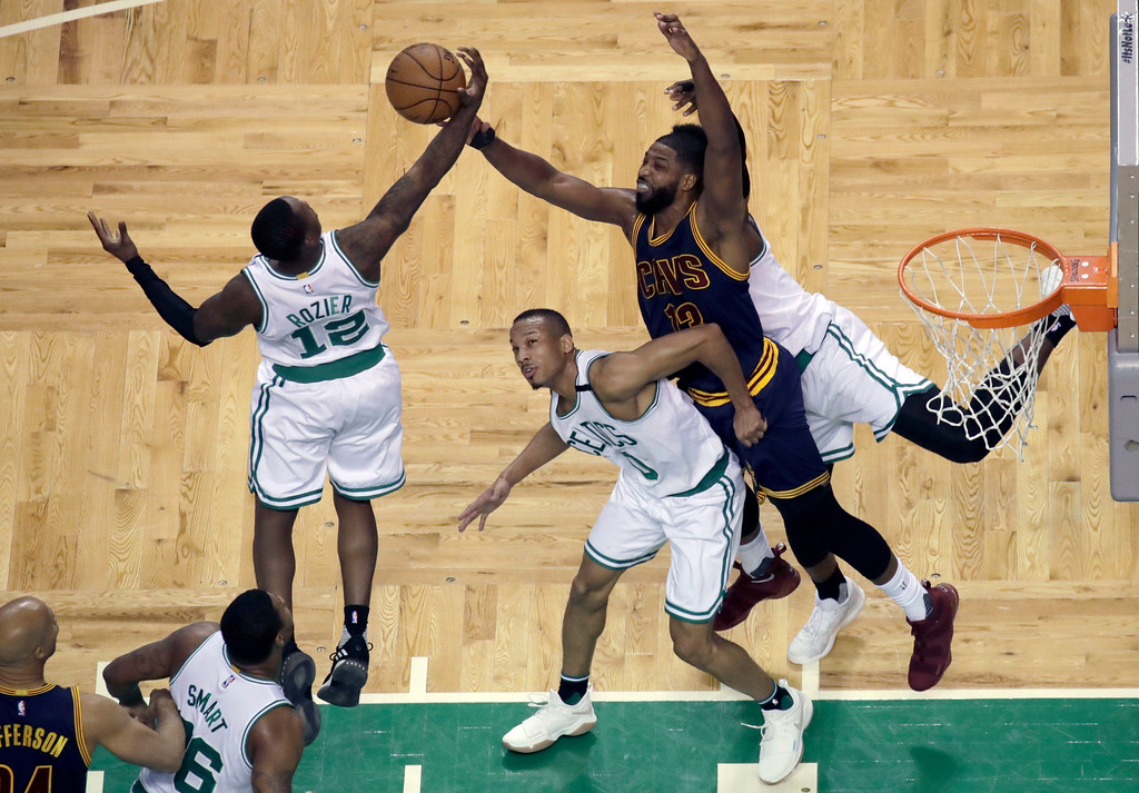 . Boston Celtics guard Terry Rozier (12) and Cleveland Cavaliers center Tristan Thompson (13) fight for a rebound over Celtics guard Avery Bradley, center, during first half of Game 2 of the NBA basketball Eastern Conference finals, Friday, May 19, 2017, in Boston. (AP Photo/Elise Amendola)