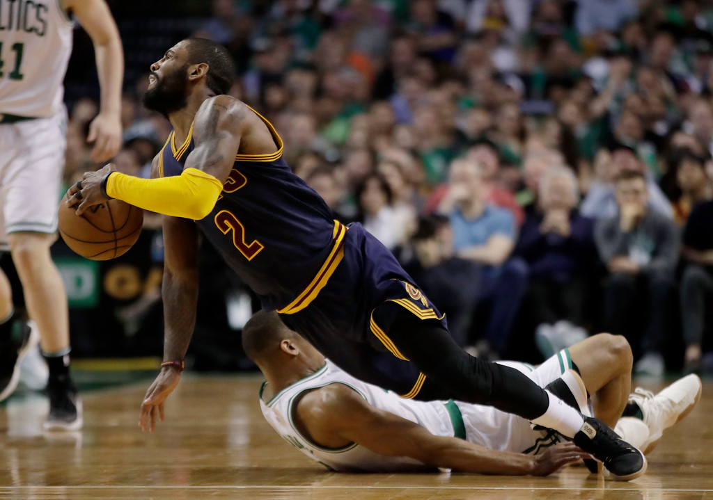 . Cleveland Cavaliers guard Kyrie Irving (2) falls with Boston Celtics guard Avery Bradley (0) during the first half of Game 2 of the NBA basketball Eastern Conference finals, Friday, May 19, 2017, in Boston. (AP Photo/Elise Amendola)
