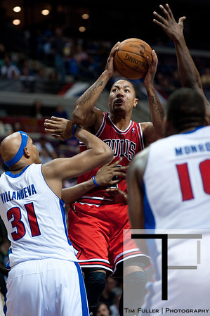 April 15, 2012; Auburn Hills, MI, USA; Chicago Bulls point guard Derrick Rose (center) goes to the basket while being guared by Detroit Pistons power forward Charlie Villanueva (31) during the first quarter at The Palace. Mandatory Credit: Tim Fuller-US PRESSWIRE