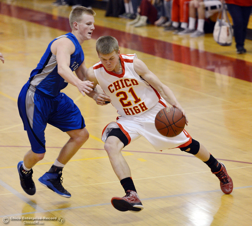 . Chico High\'s #21 Hunter Mootz (right) dribbles against Rocklin High\'s #3 Cole Bridge (left) in the second quarter of their boys basketball game at CHS Tuesday, January 7, 2014 in Chico, Calif.  (Jason Halley/Chico Enterprise-Record)
