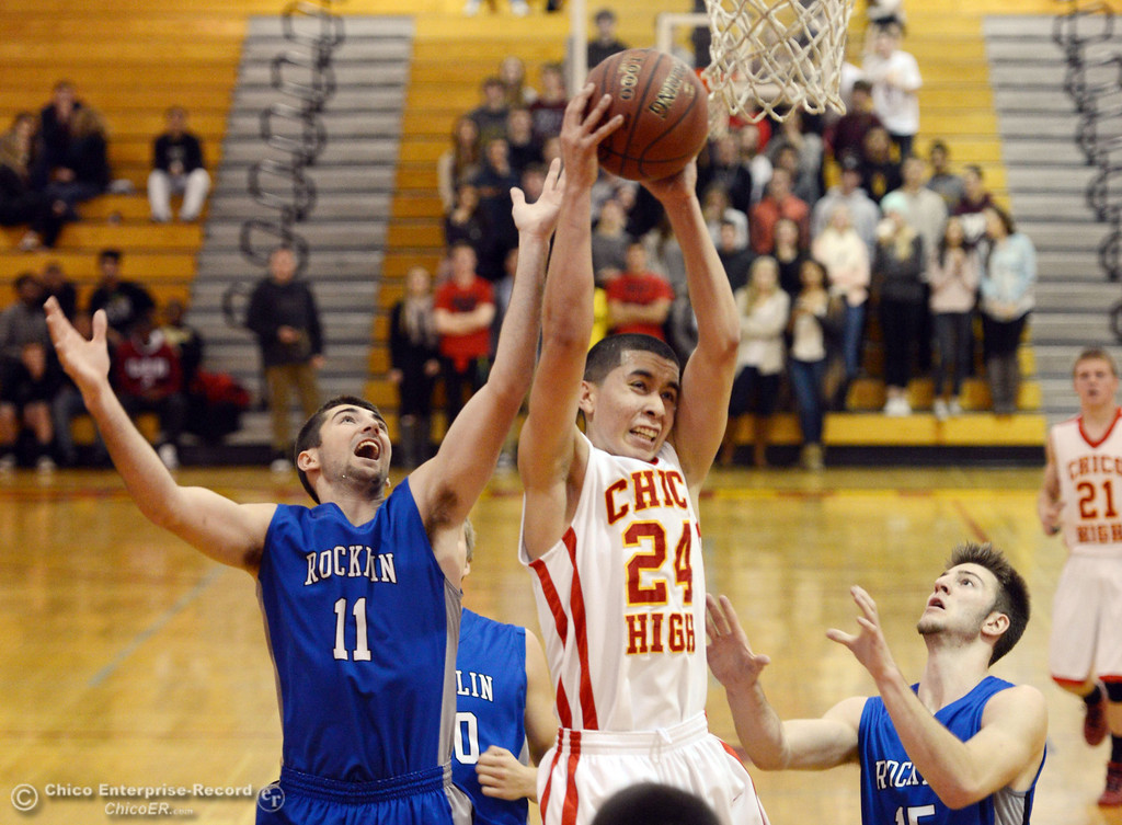 . Chico High\'s #24 Angel Roldan (center) goes up for a rebound against Rocklin High\'s #11 Tyler Chimirusti (left) and #15 Vinnie Safin (right) in the second quarter of their boys basketball game at CHS Tuesday, January 7, 2014 in Chico, Calif.  (Jason Halley/Chico Enterprise-Record)