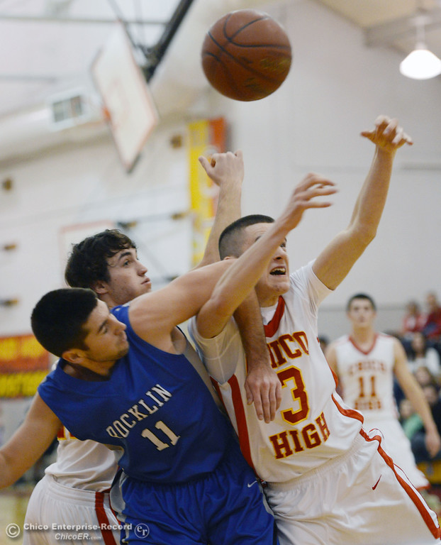 . Chico High\'s #12 Sterling Winter (left) and #3 Myles Lawing (right) get tangled up against Rocklin High\'s #11 Tyler Chimirusti (center) in the second quarter of their boys basketball game at CHS Tuesday, January 7, 2014 in Chico, Calif.  (Jason Halley/Chico Enterprise-Record)