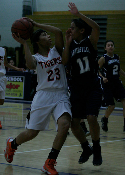 A Woodlake player drive the key against Lupe Silva of Farmersville in the Farmersville Girl's Basketball tournament.
