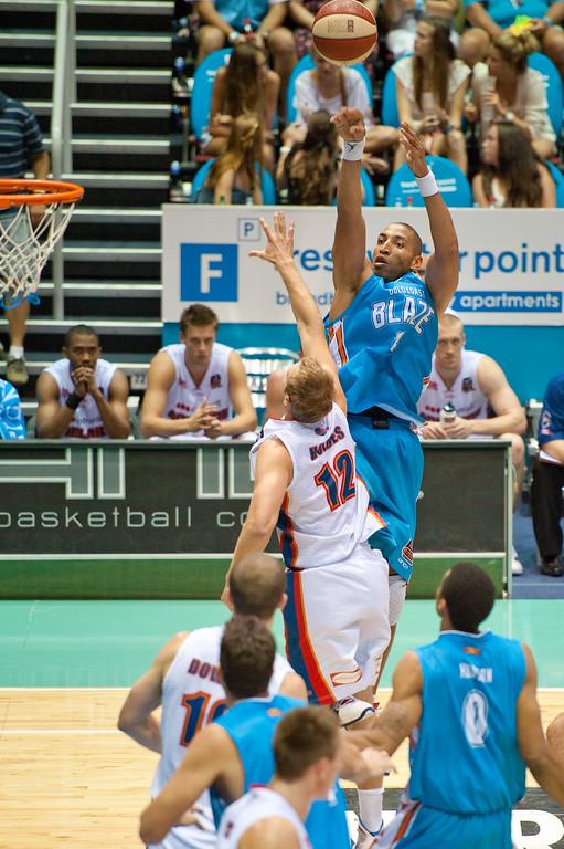 """Ira Clark shoots over Jacob Holmes - Gold Coast Blaze v Adelaide 36ers NBL Basketball; Queensland, Australia; Sunday 13 February 2011. Photos by Des Thureson:  <a href=""""http://disci.smugmug.com"""">http://disci.smugmug.com</a>"""
