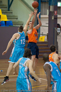Alex Loughton shows copy-book form as he shoots while under pressure from Pero Vasiljevic - Gold Coast Blaze v Cairns Taipans pre-season NBL basketball game, Saturday 18 September 2010, Carrara, Gold Coast, Australia.