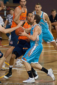 Adam Gibson takes on Daniel Dillon - Gold Coast Blaze v Cairns Taipans pre-season NBL basketball game, Saturday 18 September 2010, Carrara, Gold Coast, Australia.