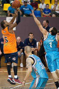 Adam Gibson closes-out on Deba George - Gold Coast Blaze v Cairns Taipans pre-season NBL basketball game, Saturday 18 September 2010, Carrara, Gold Coast, Australia.