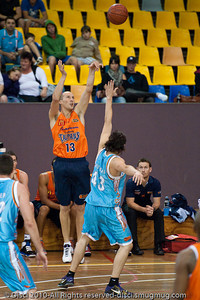 Kiwi International Phill Jones, (fresh from the World Championships in Turkey) lets-fly one of several successful three-pointers, against Chris Goulding - Gold Coast Blaze v Cairns Taipans pre-season NBL basketball game, Saturday 18 September 2010, Carrara, Gold Coast, Australia.