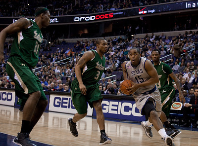 Hoyas' Austin Freeman drives past Bulls' Chris Howard. Jarrid Famous guarding the basket. Freeman ended play with 21 points.