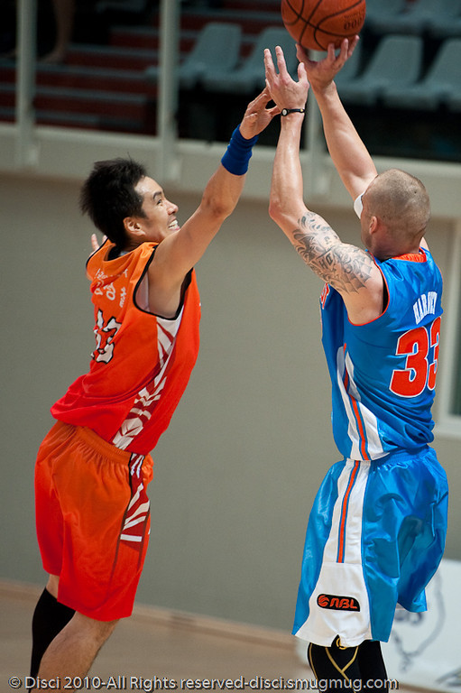 No doubt the Korean defender gets a hand to James Harvey's shot - Pre-Season NBL International Basketball: Gold Coast Blaze v Anyang KT & G Kites - Korea; Logan City, Queensland, Australia; 2010.