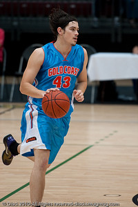 Chris Goulding runs the offence as the breeze 'sculpts' his hair - Pre-Season NBL International Basketball: Gold Coast Blaze v Anyang KT & G Kites - Korea; Logan City, Queensland, Australia; 2010.