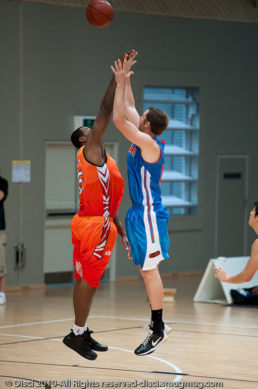 No doubt the Korean defender gets a hand to Anthony Petrie's shot - Pre-Season NBL International Basketball: Gold Coast Blaze v Anyang KT & G Kites - Korea; Logan City, Queensland, Australia; 2010.