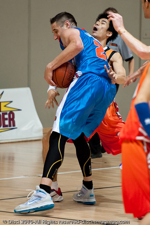 The Korean defender 'sells' the charge - Pre-Season NBL International Basketball: Gold Coast Blaze v Anyang KT & G Kites - Korea; Logan City, Queensland, Australia; 2010.