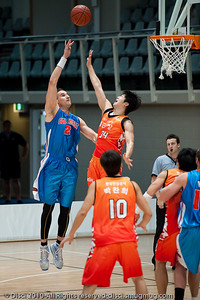 Pero Vasiljevic goes inside against a committed leap from the defender - Pre-Season NBL International Basketball: Gold Coast Blaze v Anyang KT & G Kites - Korea; Logan City, Queensland, Australia; 2010.