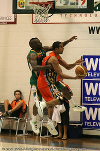 "Canadian Olympian Dave Thomas (""DT"") tries to score, as defender Corey Williams tries to take the '3 point play' out of the equation - Cairns NBL pre-season basketball tournament; Tropical North Queensland, Australia; August 2008."