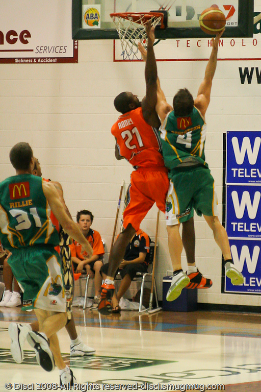 Townsville Crocs Point Guard Kelvin Robertson goes strong to the basket against forward Larry Abney  - Cairns NBL pre-season basketball tournament; Tropical North Queensland, Australia; August 2008.