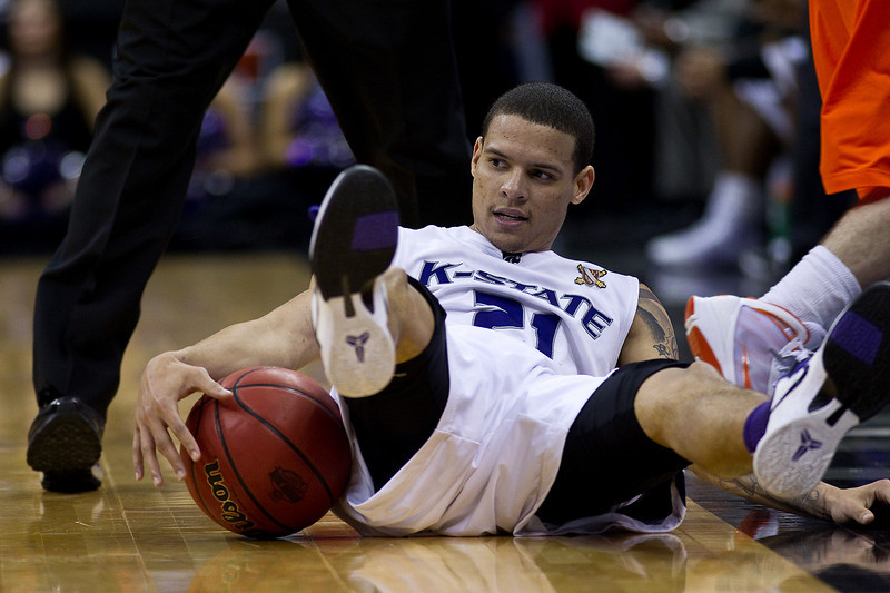11 March 2010: Kansas State Wildcats guard Denis Clemente (21) gets fouled and goes down to the floor during the quarterfinals of the Phillips 66 Big 12 Men's Basketball Championship.  The Kansas State Wildcats defeated the Oklahoma State Cowboys 83-64 at Sprint Center in Kansas City, Missouri.