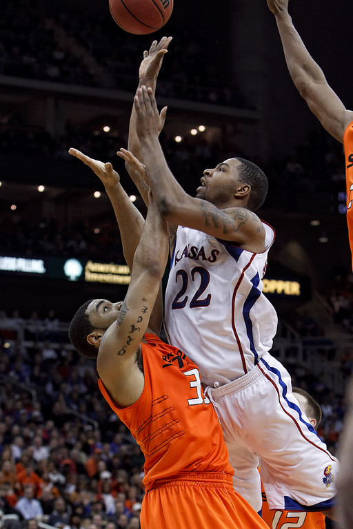 March 10, 2011: Kansas Jayhawks forward Marcus Morris (22) goes up for a shot while Oklahoma State Cowboys forward Marshall Moses (33) tries to draw a charge during the quarterfinals of the Phillips 66 Big 12 Men's Basketball Championship.  The Kansas Jayhawks defeated the Oklahoma State Cowboys 62-63 at Sprint Center in Kansas City, Missouri.