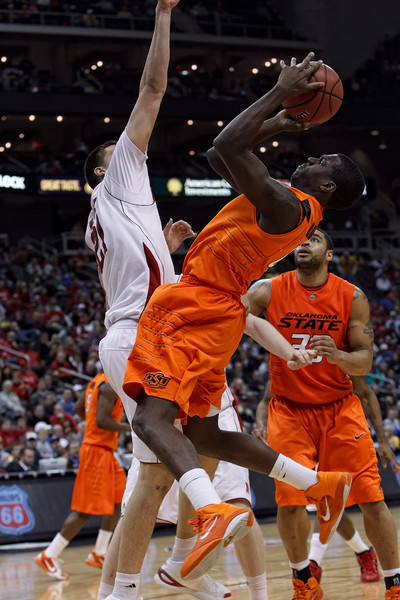 March 9, 2011: Oklahoma State Cowboys forward J.P. Olukemi (0) attempts a shot in front of Nebraska Cornhuskers center Jorge Brian Diaz (21) during the first round of the Phillips 66 Big 12 Men's Basketball Championship.  The Oklahoma State Cowboys defeated the Nebraska Cornhuskers 53-52 at Sprint Center in Kansas City, Missouri.