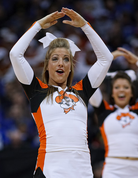 """March 10, 2011: An Oklahoma State cheerleader with a black eye entertains makes an """"O"""" with her arms during the quarterfinals of the Phillips 66 Big 12 Men's Basketball Championship.  The Oklahoma State Cowboys led the Kansas Jayhawks 41-35 at the half at Sprint Center in Kansas City, Missouri."""