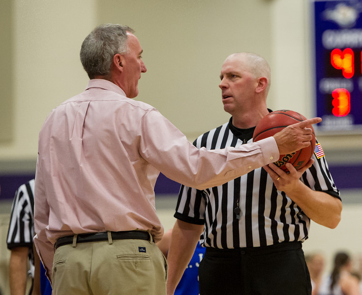 Head Coach Mike McDevitt has a discussion with one of the officials during the Women's Basketball game between Saint Joseph's (ME) and Curry Collage at Curry College, Milton, Massachusetts, USA on November 16, 2013. Photo: Chris Poss