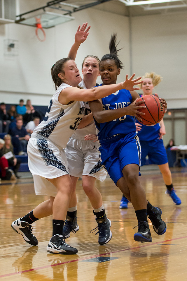 Sarah Assante (20) drives for a layup with Abby Young (12) in the background during the Women's Basketball game between Saint Joseph's (ME) and Rivier University at Rivier University, Nashua, New Hampshire, USA on January 12, 2013. Photo: Chris Poss
